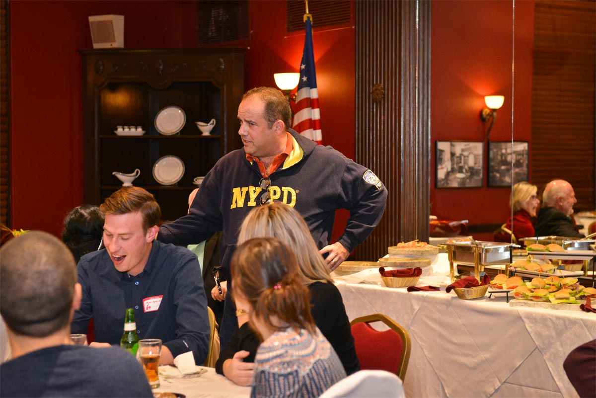 A man in an NYPD jacket addressing a dining room full of people
