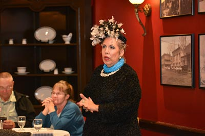 A woman in an elaborate hat, speaking to a group