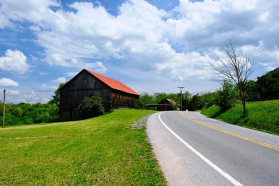 Paved highway in rural setting with a barn