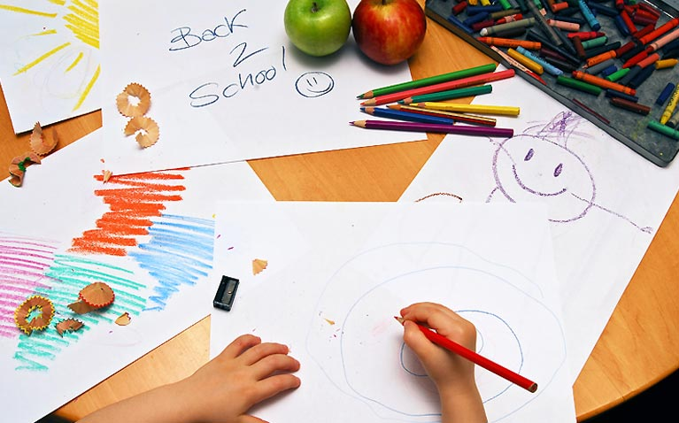 Hands of a child drawing school pictures