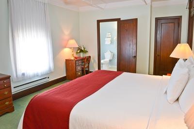 King room with bed and bathroom viewed through open door.