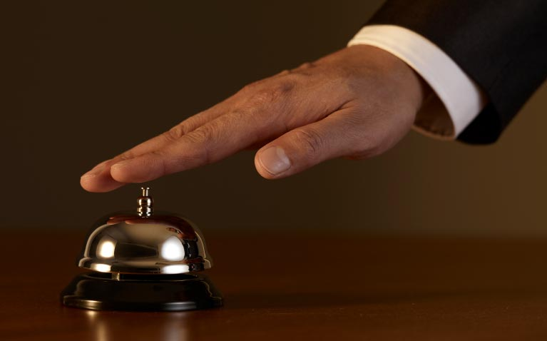 A hand about to ring a service bell